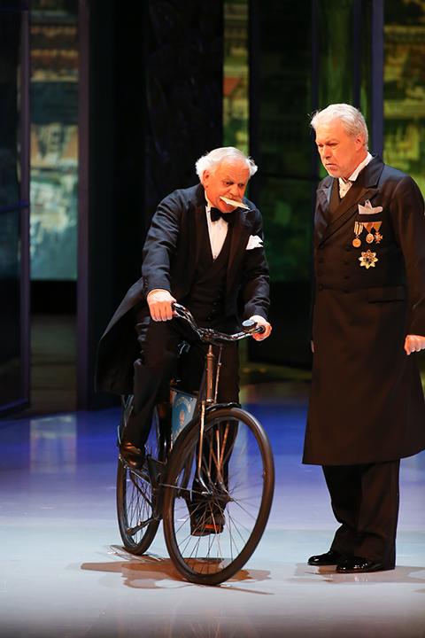"""小国ポンテヴェドロの""""公用車""""は自転車 マイヤー扮するニェーグシュは、この""""公用車""""で登場する度に笑いを誘う Photo:Kiyonori Hasegawa"""