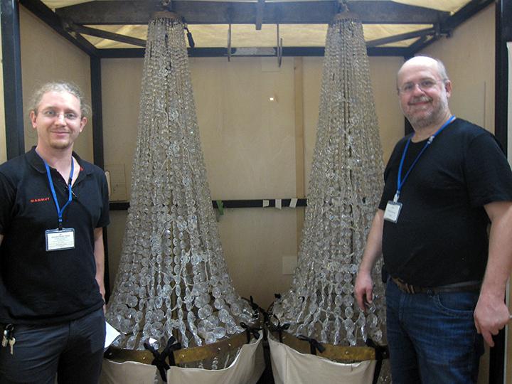木箱を開けてシャンデリアを見せてくれる照明スタッフ(右)と舞台スタッフ(左)