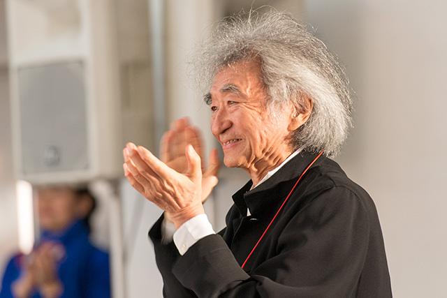 成城学園初等学校合唱部の歌に拍手をおくる小澤征爾