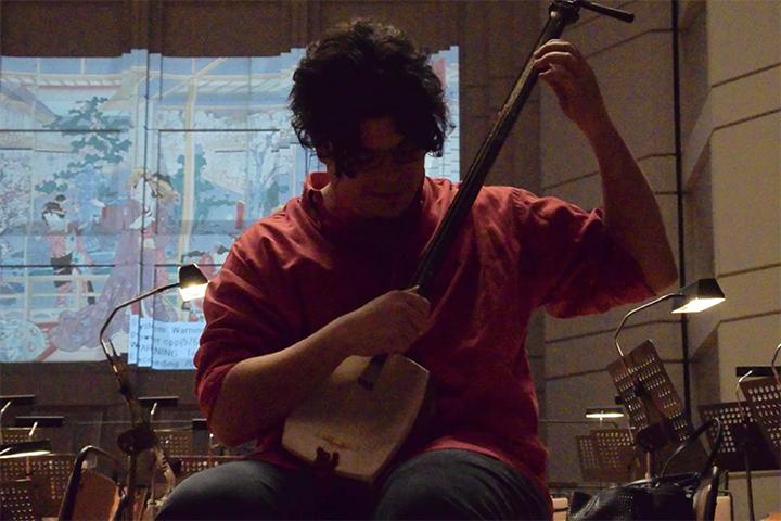 イリスが使う小道具の三味線を試奏するバッティストーニ